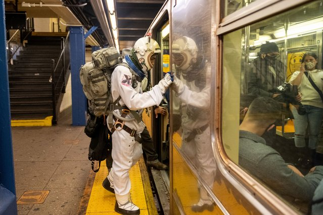 Andy Saturn dressed in a space outfit walks in through a subway station over memorial day weekend on May 29, 2021 in New York City. On May 19, 2021 all pandemic restrictions, including mask mandates, social distancing guidelines, venue capacities and restaurant curfews were lifted by New York Governor Andrew Cuomo. (Photo by Alexi Rosenfeld/Getty Images)