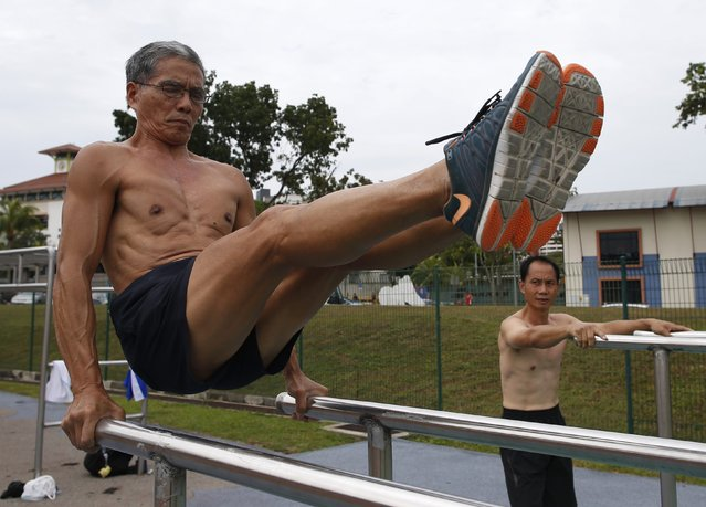 Team Strong Silvers member Ngai Hin Kwok, 66, works out as teammate Ng Siu Chi, 57, watches at a stadium in Singapore March 15, 2015. Team Strong Silvers, is a group of senior citizens who train in calisthenics. The trio trains individually at least three times a week, and meets up for joint calisthenics at least twice a month. (Photo by Edgar Su/Reuters)