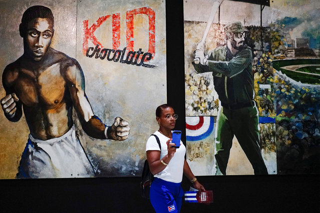 Wrestling athlete Yudari Sanchez, 20, takes a selfie next to images depicting Cuban late President Fidel Castro (R) and late Cuban boxer Kid Chocolate at the Cuban Sports Hall after its inauguration in Havana, Cuba, July 13, 2018. (Photo by Alexandre Meneghini/Reuters)