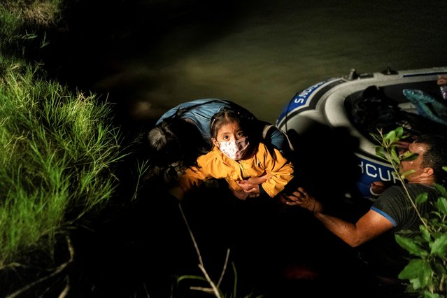 Asylum-seeking migrants' families disembark an inflatable raft after crossing the Rio Grande river into the United States from Mexico in Roma, Texas, U.S., June 10, 2021. (Photo by Go Nakamura/Reuters)