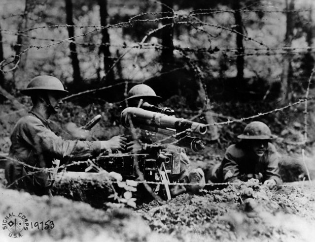 """American soldiers manning a French """"37"""", a one-pounder in firing position behind barbed wire in a second line trench at Dieffmatten, in Alsace, 26th June 1918. (Photo by Allen H. Hanson/Hulton Archive/Getty Images)"""