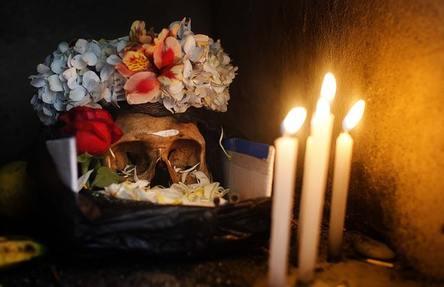 A decorated human skull is illuminated by candlelight during the Natitas Festival. (Photo by Juan Karita/Associated Press)
