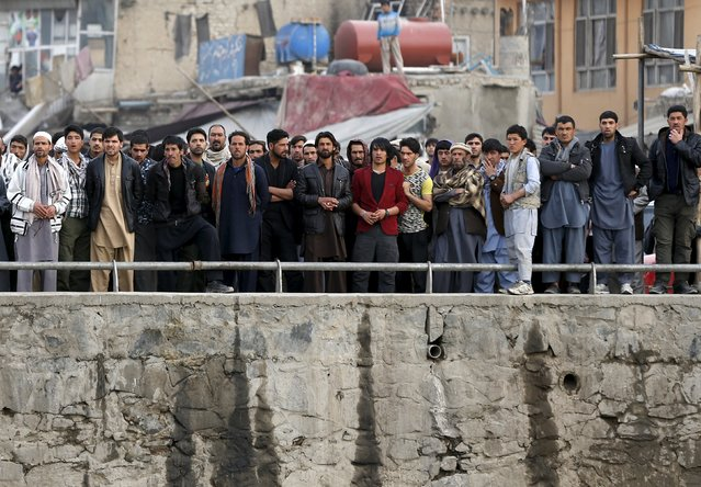 Afghan residents look as security forces inspect the site of a suicide attack in Kabul March 25, 2015. (Photo by Omar Sobhani/Reuters)