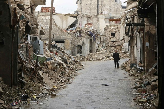 A man walks through a damaged street beside a frontline in Old Aleppo January 4, 2015. (Photo by Hosam Katan/Reuters)