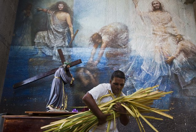 A church volunteer carries an armful of palm fronds to be given to parishioners as they arrive to attend a Palm Sunday celebration at the Metropolitan Cathedral, in Managua, Nicaragua, Sunday, March 29, 2015. (Photo by Esteban Felix/AP Photo)