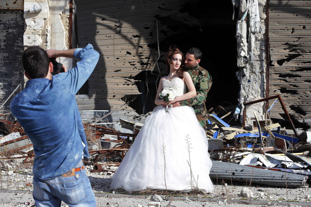 Newly-wed Syrian couple Nada Merhi, 18, and Hassan Youssef, 27, have their wedding pictures taken in front of a heavily damaged building in the war ravaged city of Homs on February 5, 2016. A Syrian photographer thought of using the destruction of Homs to take pictures of newly wed couples to show that life is stronger than death. (Photo by Joseph Eid/AFP Photo)
