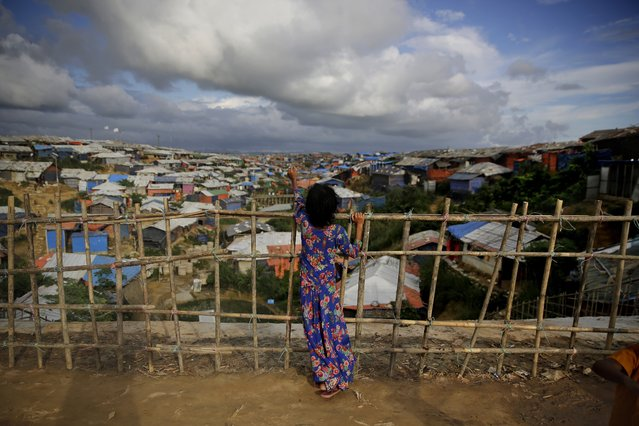 In this August 26, 2018, photo, a Rohingya refugee girl stands by a fence at Kutupalong refugee camp, Bangladesh. (Photo by Altaf Qadri/AP Photo)