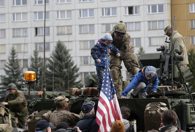 A US army soldier helps a kid on top of a stryker armored vehicle during a stop of his convoy in Prague, Czech Republic, Tuesday, March 31, 2015. (Photo by Petr David Josek/AP Photo)