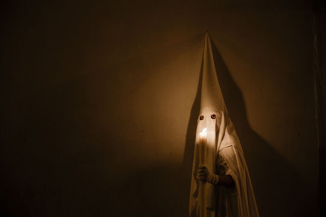 "A penitent taking part in ""Nuestro Senor Atado a la Columna, Maria Santisima de la Paz y San Juan Evangelista"" Holy Week procession, holds a big candle in Arcos de la Frontera, Spain, Tuesday, March 31, 2015. (Photo by Daniel Ochoa de Olza/AP Photo)"