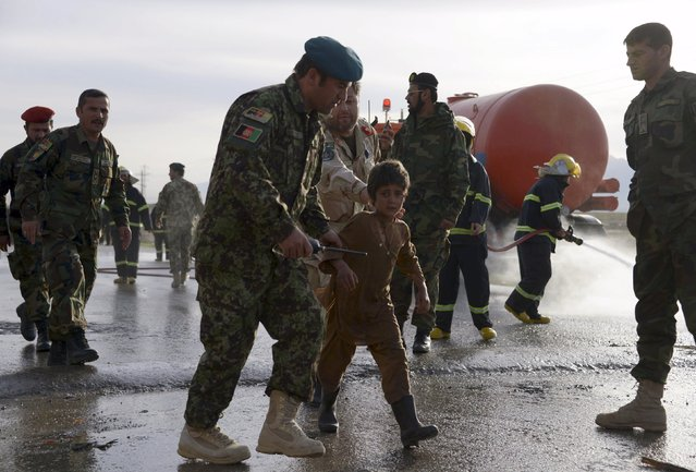An Afghan National Army officer escorts a slightly injured boy from the site of a suicide attack on the outskirts of Mazar-i-Sharif, Afghanistan February 8, 2016. (Photo by Anil Usyan/Reuters)