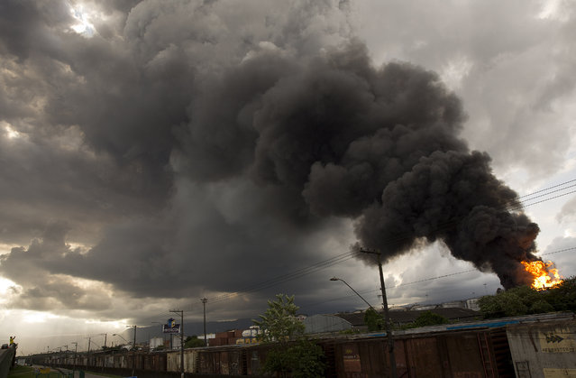 Smoke rises from a fire at a liquid bulk storage facility near Brazil's port of Santos, Thursday, April 2, 2015. The fire broke out Thursday morning at the facility owned by Ultracargo, one of Brazil's largest liquid bulk storage companies. Fuels, chemicals, vegetable oils, ethanol and corrosive products are stored at the site. The Santos fire department said there are no fatalities and that two workers were treated for smoke inhalation. (Photo by Andre Penner/AP Photo)