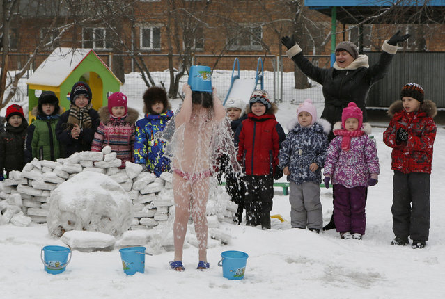 Children watch their classmate pour cold water on herself, under the watch of fitness coach Oksana Kabotko (not pictured), as part of a health and fitness program at a local kindergarten in subzero temperatures, in Krasnoyarsk, Siberia, Russia, February 9, 2016. (Photo by Ilya Naymushin/Reuters)