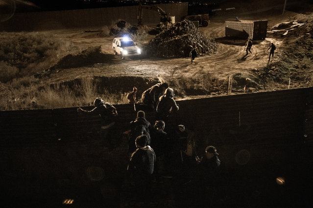 A border patrol officer is overpassed by migrants running while others already climbing the U.S. border fence jump inside the United States to San Diego, from Tijuana, Mexico, Tuesday, December 25, 2018. Discouraged by the long wait to apply for asylum through official ports of entry, many Central American migrants from recent caravans are choosing to cross the U.S. border wall and hand themselves into border patrol agents. (Photo by Daniel Ochoa de Olza/AP Photo)