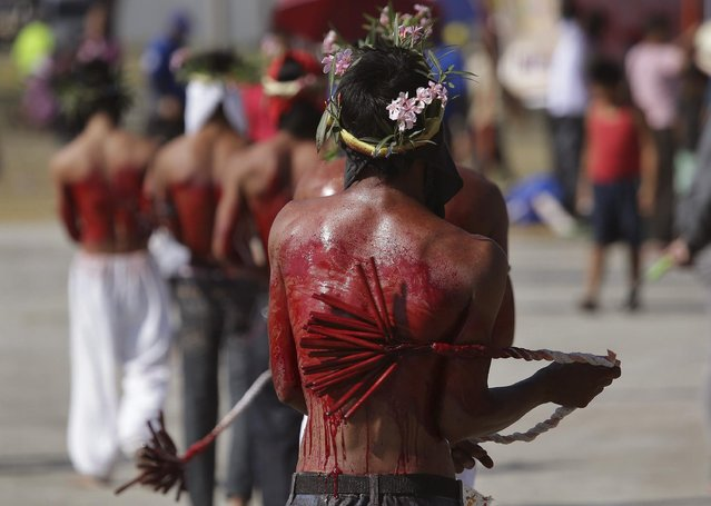 Hooded Filipino penitents hit their back with wooden sticks during Good Friday rituals to atone for sins on April 3, 2015 in Pampanga province, northern Philippines. (Photo by Aaron Favila/AP Photo)