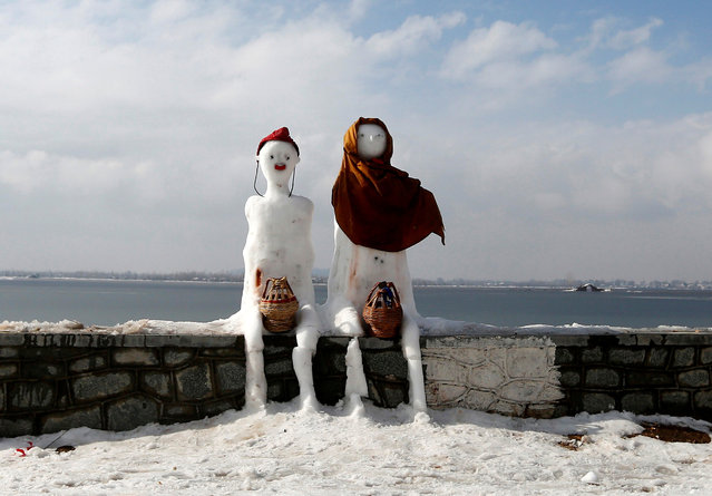 "A snow man and a snow woman with ""Kangris"", traditional fire pots, are installed on the banks of Dal Lake in Srinagar January 8, 2017. (Photo by Danish Ismail/Reuters)"