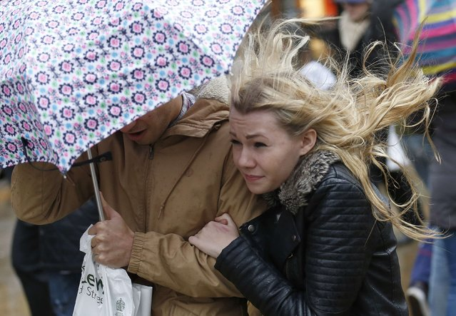 Shoppers walk in wet and windy weather on Oxford Street in central London December 23, 2013. British retailers risked missing out on the traditional pre-Christmas rush on Monday as dire weather hit the country, potentially putting off millions of shoppers holding out for last-minute discounts. (Photo by Olivia Harris/Reuters)