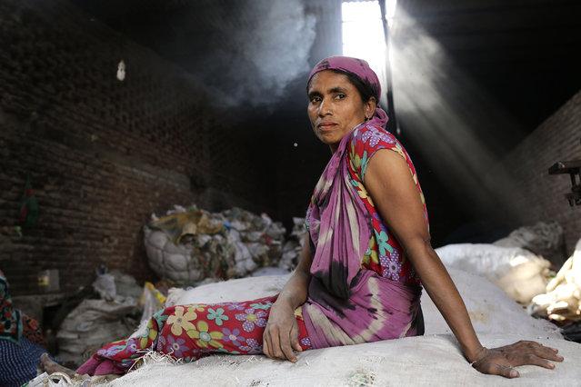 Monowara Begum takes rest during the lunch break while working in a small factory in Dhaka, Bangladesh, 22 February 2016. Monowara earns around 65 euro per month after working 12 hours per day. She has moved to the capital from Bhola after they lost their house from river erosion. Many internal migrated female workers work with unsafe conditions in many small factory and without proper wages. (Photo by Abir Abdullah/EPA)