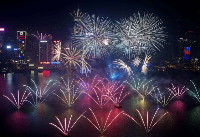 Fireworks explode over Victoria Harbour and the Hong Kong Convention and Exhibition Centre. (Photo by Tyrone Siu/Reuters)