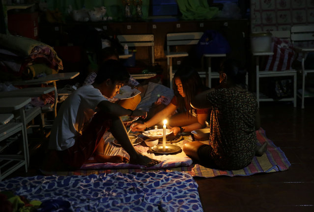 A family shares a meal using a flashlight inside a temporary evacuation center as electricity was shut-off following the onslaught of Typhoon Mangkhut in Tuguegarao city in Cagayan province, northeastern Philippines, Saturday, September 15, 2018. The typhoon slammed into the Philippines northeastern coast early Saturday, it's ferocious winds and blinding rain ripping off tin roof sheets and knocking out power, and plowed through the agricultural region at the start of the onslaught. (Photo by Aaron Favila/AP Photo)