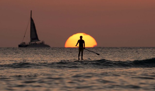 A paddle boarder looks our over the Pacific Ocean as the sun sets off of Waikiki Beach, in Honolulu, on New Years Eve, Tuesday, December 31, 2013. President Barack Obama and the first family are in Hawaii for their annual holiday vacation. (Photo by Carolyn Kaster/AP Photo)