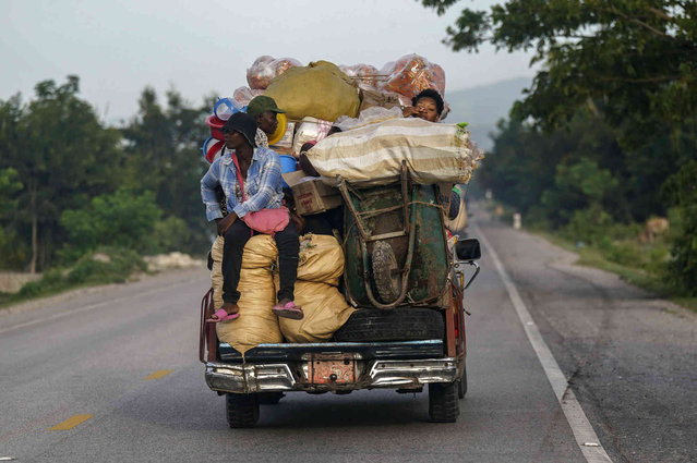 Venders travel with their goods on the first market day since the earthquake in Camp Perrin, Haiti, Friday, August 20, 2021, six days after a 7.2 quake. (Photo by Fernando Llano/AP Photo)