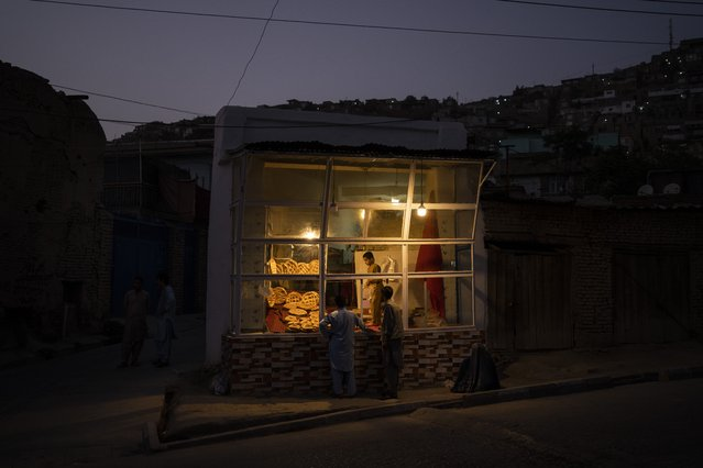 Customers wait outside a small bakery at dusk in Kabul, Afghanistan, Friday, September 10, 2021. (Photo by Bernat Armangue/AP Photo)