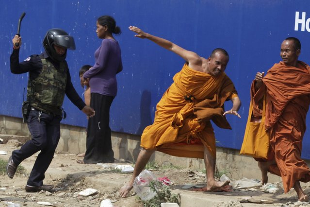 A security guard chases away Buddhist monks from camp occupied by anti-government demonstrators in Phnom Penh on January 4, 2014. (Photo by Reuters/Stringer)