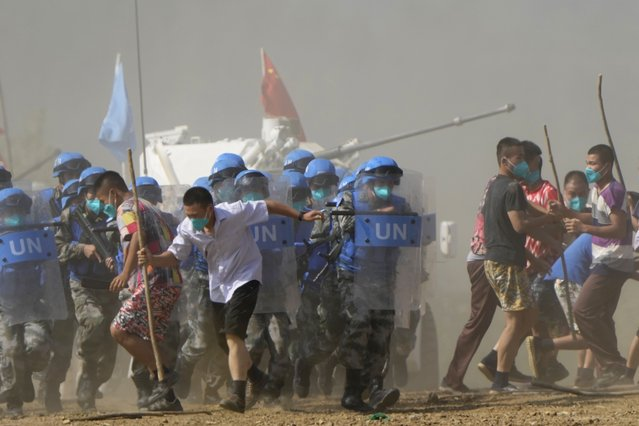 United Nations troop break up fighting in a scenario where participants playing the role of civilians fighting over water resource during the Shared Destiny 2021 drill at the Queshan Peacekeeping Operation training base in Queshan County in central China's Henan province  Wednesday, September 15, 2021. Peacekeeping troops from China, Thailand, Mongolia and Pakistan took part in the 10 days long exercise that field reconnaissance, armed escort, response to terrorist attacks, medical evacuation and epidemic control. (Photo by Ng Han Guan/AP Photo)