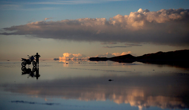 A local man stops with his motorbike to enjoy the sun set over the Salar de Uyuni or Uyuni Salt Flat during Day 7 of the 2014 Dakar Rally on January 11, 2014 in Uyuni, Bolivia. (Photo by Dean Mouhtaropoulos/Getty Images)