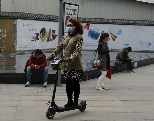 A woman wearing a mask rides an electronic scooter on a hazy day at a business district in Beijing April 10,  2015. (Photo by Kim Kyung-Hoon/Reuters)