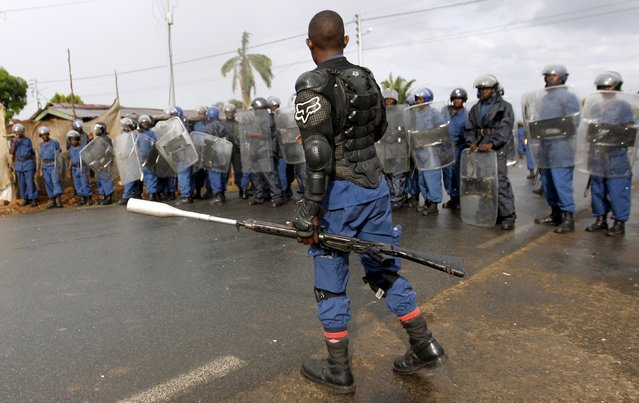 Riot policemen stand in formation during street protests against the decision made by Burundi's ruling National Council for the Defence of Democracy-Forces for the Defence of Democracy (CNDD-FDD) party to allow President Pierre Nkurunziza to run for a third five-year term in office, in the capital Bujumbura, April 26, 2015. (Photo by Thomas Mukoya/Reuters)