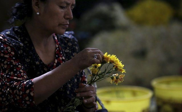 A florist arranges flowers at the Piedra Liza flower market in Lima April 29, 2015. (Photo by Mariana Bazo/Reuters)