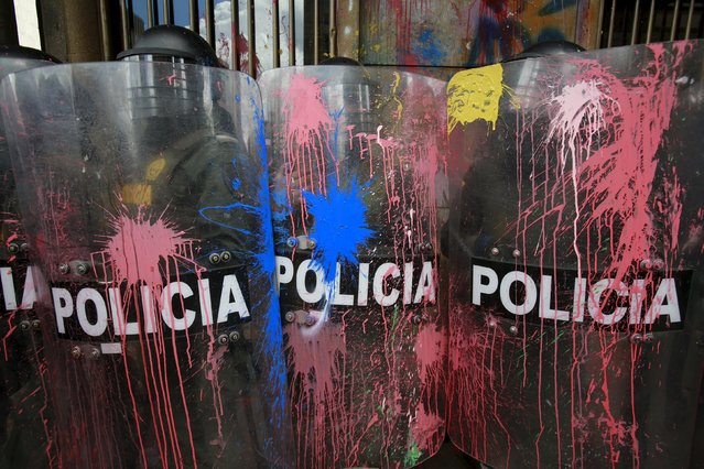 Riot policemen stand with their shields stained with pain by students during a nationwide strike against the government's education, labour and health policies in Bogota, Colombia, March 17, 2016. (Photo by John Vizcaino/Reuters)