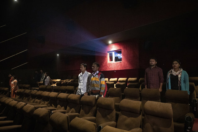 In this Monday, November 26, 2018 photo, moviegoers stand as national anthem is played at a cinema before the screening of a movie in Lucknow, Uttar Pradesh, India. As with similar movements across the world, Hindu nationalism, once fringe, has now taken a central place in India's politics. (Photo by Bernat Armangue/AP Photo)