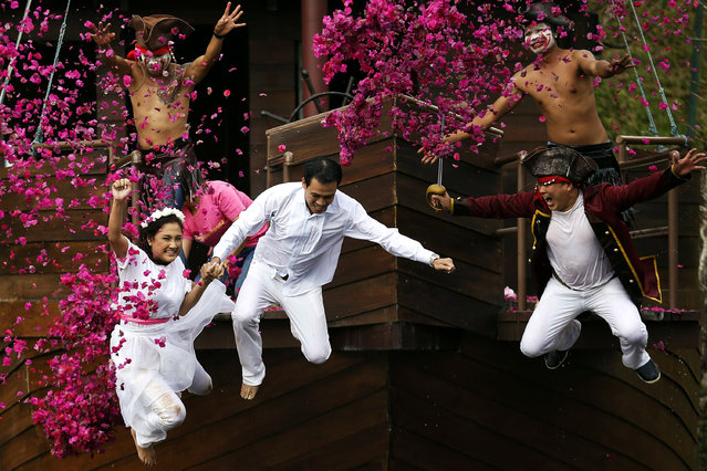 Groom Roongroj Walailuk and bride Vina Wichan jump into the pond as they are chased by men dressed as pirates during a wedding ceremony ahead of Valentine's Day in Prachin Buri province, east of Bangkok February 13, 2014. Three Thai couples took part in the wedding ceremony which was arranged by a resort and aimed at strengthen the relationships of the couples through fun activities. (Photo by Damir Sagolj/Reuters)