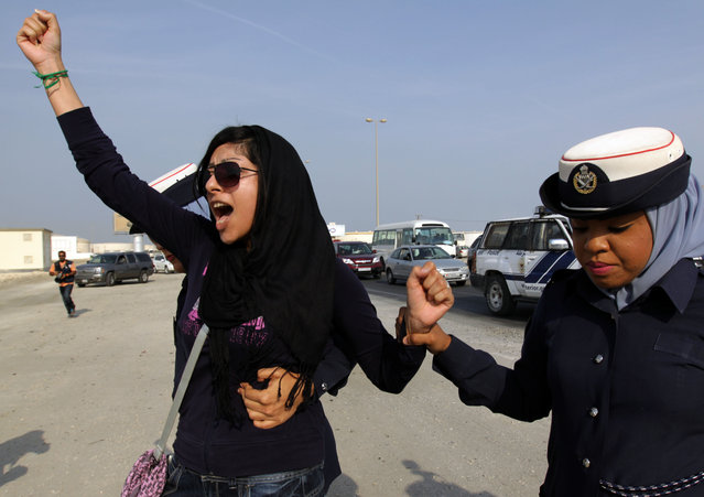 "In this October 21, 2012 file photo, Bahraini opposition activist Zainab al-Khawaja, left, gestures as she shouts ""God is greater than any tyrant"", while being arrested by police officers in Eker, Bahrain. On Friday, March 18, 2016, Michel Forst, the U.N. special rapporteur on the situation of human rights defenders, called on Bahrain to release al-Khawaja and her son, Abdulhadi. (Photo by Hasan Jamali/AP Photo)"