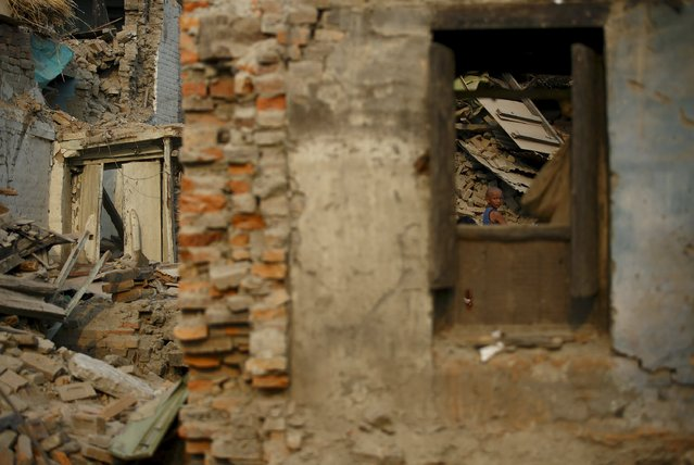 A boy is seen through the window of a collapsed house after the April 25 earthquake at Bhaktapur May 7, 2015. (Photo by Navesh Chitrakar/Reuters)