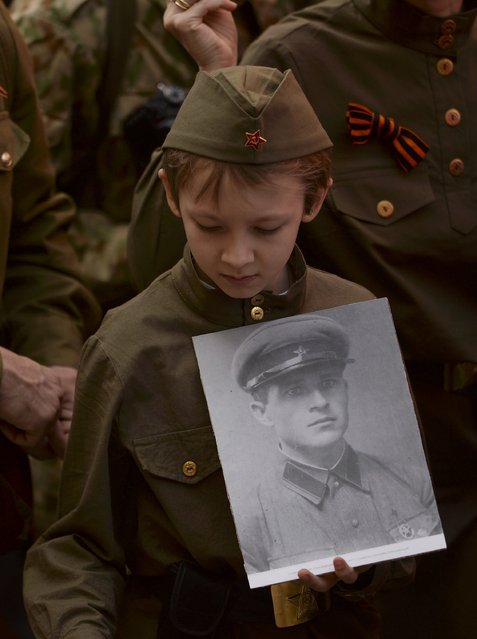 A boy holds a portrait of his relative during the Immortal Regiment march in Moscow, Russia, May 9, 2015. (Photo by Reuters/Host Photo Agency/RIA Novosti)