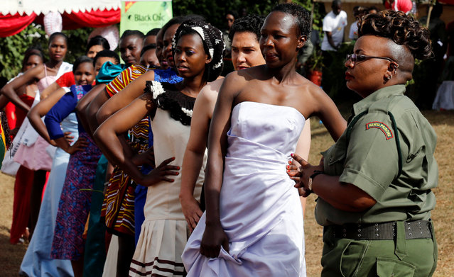 """A prison warden organises female inmates for participating in a fashion parade as part of their Valentine's Day celebration, dubbed """"love behind bars"""" inside the Langata Women Maximum Security Prison in Kenya's capital Nairobi, February 14, 2017. (Photo by Thomas Mukoya/Reuters)"""