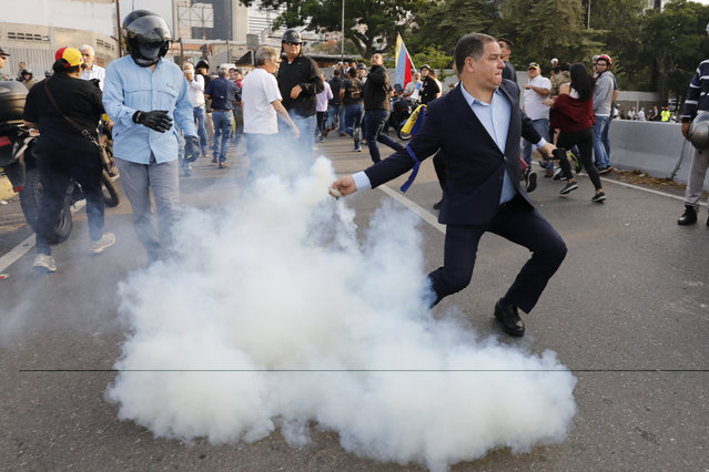 An opponent to Venezuela's President Nicolas Maduro returns a tear gas canister in Caracas, Venezuela, Monday, April 29, 2019. Venezuelan opposition leader Juan Guaido appeared in a video with a small contingent of armed soldiers and formerly detained opposition activist Leopoldo Lopez calling for Venezuelans to take to the streets to oust Maduro. (Photo by Ariana Cubillos/AP Photo)