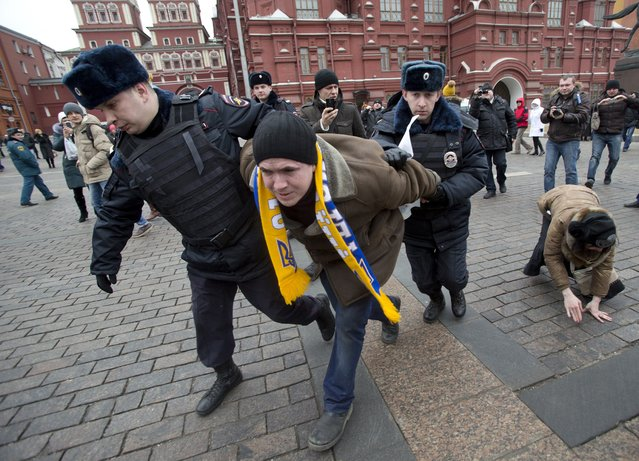 Police detain an activist protesting against recent developments in Russian-Ukrainian relations during an unsanctioned rally on the Manezh Square in Moscow, Russia, Sunday, March 2, 2014. (Photo by Pavel Golovkin/AP Photo)