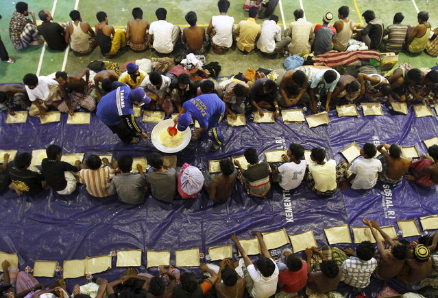 Indonesian Rescue Team members distribute food to migrants believed to be Rohingya inside a shelter after they were rescued from boats, in Lhoksukon in Indonesia's Aceh Province May 11, 2015. (Photo by Roni Bintang/Reuters)