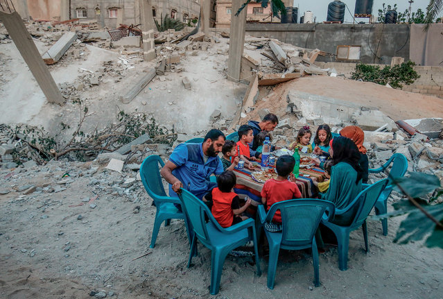 A Palestinian family break their fast next to their house that was destroyed during the two-day escalation, in Rafah the southern Gaza Strip on May 8, 2019. Palestinian leaders in Gaza agreed to a ceasefire with Israel on May 6, 2019 to end a deadly two-day escalation in violence that threatened to widen into a fourth war between them since 2008. (Photo by Said Khatib/AFP Photo)