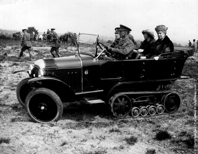 Queen Mary with Princess Mary, the Princess Royal being driven across rough ground in a tracked car by Army officers