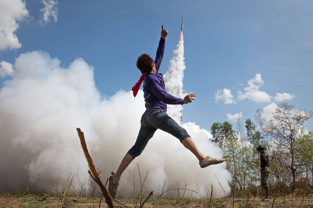 A young Thai man jumps in the air and cheers as his rocket takes off at the Bun Bang Fai Rocket Festival on May 10, 2015 in Yasothon, Thailand. During the Bun Bang Fai rocket festival, Thai residents launch enormous home-made rockets into the air to gain Buddhist merit and to celebrate the beginning of the rainy season. (Photo by Taylor Weidman/Getty Images)