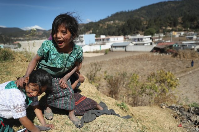 Young girls, who's father works as as immigrant laborer in the U.S., play in Cajola on February 11, 2017 in the western highlands of Guatemala. Women are especially effected by emigration from Guatemala, where some 70 percent of the men have left to work as undocumented immigrants in the United States, many of them leaving behind wives and children who only know their fathers online, if at all. Grupo Cajola, an NGO funded by American donations, is attempting to make the town's economy prosper locally to help reduce the need for emigration. With U.S. President Donald Trump's crackdown on illegal immigration, the spectre of increased deportations back to Guatemala and reduced remittances has made the need to educate children and adults and transform the local economy more urgent than ever. Remitances from undocumented Guatemalan laborers are the main source of income of Guatemala, and while increasing family wealth and driving a housing boom in towns like Cajola, they have also had the negative effect tearing the social fabric of local communites. Grupo Cajola has set up a weaving center, an egg farm, carpentry shop, internet cafe, library and education programs for pre-schoolers and their parents, while providing scholarships for more than 20 young residents to learn local trades. Textiles they produce are now exported for sale to the U.S. Grupo Cajola was founded in 2000 by Eduardo Jimenez, who lived as an undocumented immigrant for 10 years in the U.S. before returning to Guatemala. He coordinates locally with the group's American director Caryn Maxim, who organizes funding and product sales in New Jersey. (Photo by John Moore/Getty Images)