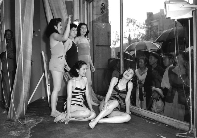 To draw the public's attention to a new line of bathing suits, a Tokyo department store used live models to show off the suits on June 5, 1950. The rain didn't bother the curious, and both the girls and the crowd seemed to like the idea of staring at each other through the glass. (Photo by AP Photo via The Atlantic)