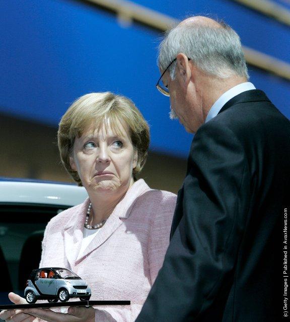 German Chancellor Angela Merkel holds a model of a Smart car