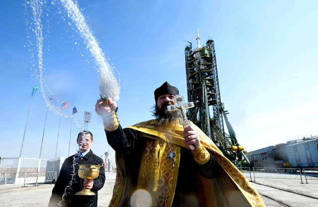 "An Orthodox priest baptizes the ""Soyuz"" rocket at the Baikonur space center in Kazakhstan on March 24, 2014. (Photo by Joel Kowsky/NEWSCOM/SIPA Press)"