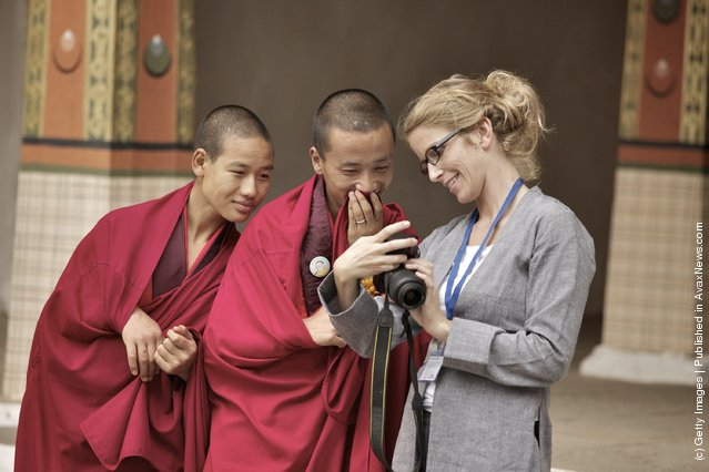 Young monks laugh at their own photos taken by a German photojournalist in the main courtyard of the Dzong
